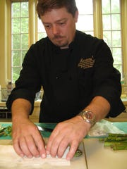 Chef John Strand wraps asparagus in filo dough for a dish he is preparing for a customer.