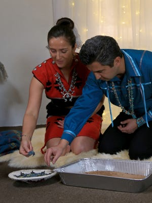 Rachael and Pooya Rezai eat blue corn mush during their traditional Navajo wedding ceremony in a hogan on the Navajo Nation Reservation.