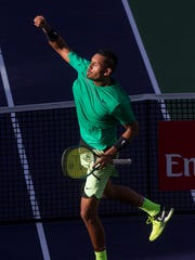 Nick Kyrgios celebrates his win over Novak Djokovic