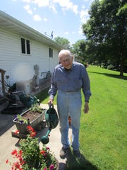 Father Edward Sippel waters his plants at his home in Fond du Lac.