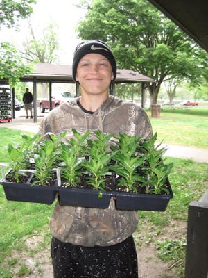 Jason Bartley smiles while helping with the Adena Women's Board's annual flower sale for a class community service project during his sophomore year at Pickaway-Ross Career and Technology Center.