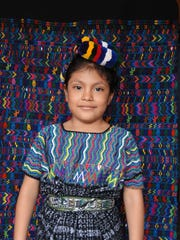 The weaver's daughter in San Miguel Chicaj poses in