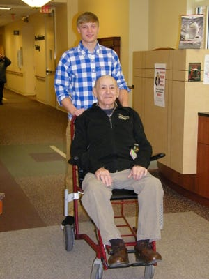 Dillon Berkey, a volunteer at The Bellevue Hospital, pushes Buzz Dayringer. Berkey's duties also include greetings guests at the front desk and delivering paperwork.