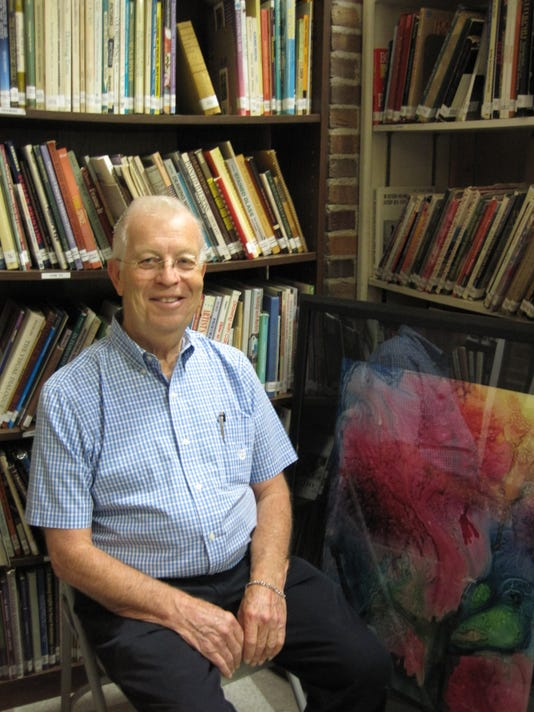 Tom Hart art volunteer of the year sitting in the art library he manages wit.JPG