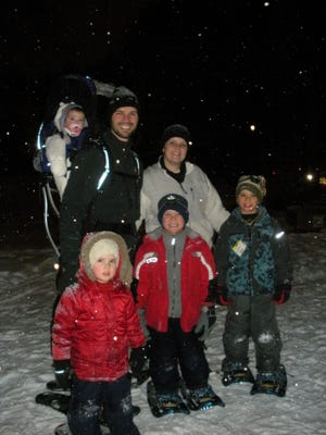 A family is dressed for snowshoeing at the Monk Gardens on a past candlelit hike.