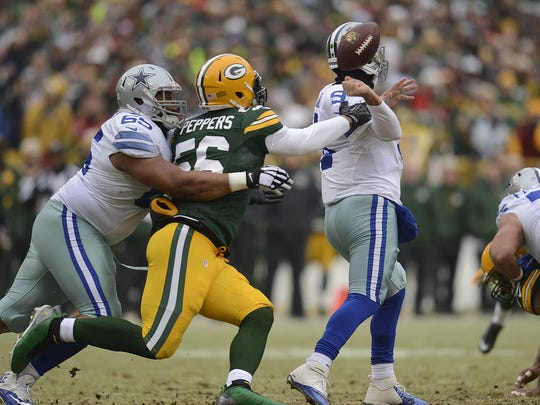 Green Bay Packers linebacker Julius Peppers (56) knocks the ball from Dallas Cowboys quarterback Tony Romo's hand in the first quarter during Sunday's NFC divisional playoff game at Lambeau Field.  Evan Siegle/Press-Gazette Media