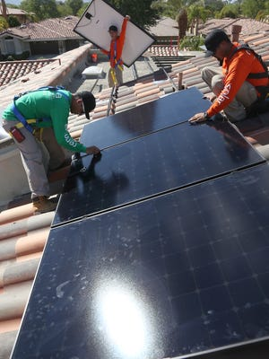 Renova Solar workers install an 8,000-watt solar system at a home in Indian Ridge Country Club in Palm Desert.