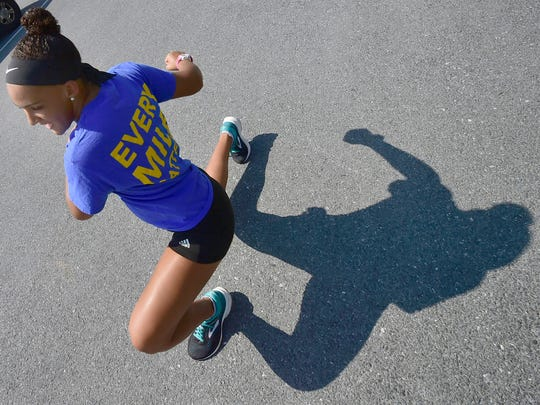 Monica Henderson warms up before a run in Chambersburg. Henderson, who just completed her first year as a University of Pittsburgh student, will be participating in a run across the country to raise money for cancer. She is a childhood cancer survivor.
