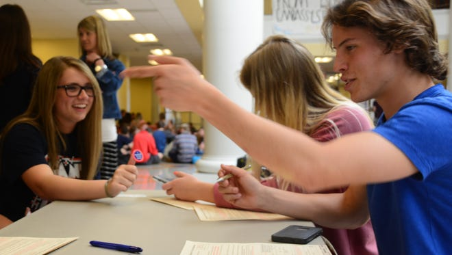 Summit High School senior Kendall Stewart, left, helps students like Teagan Lenox, right, register to vote.