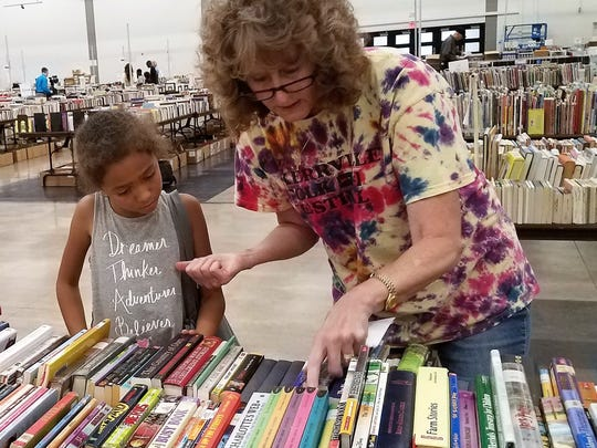 Children who went to select books were guided Wednesday by adults to find appropriate and interesting reading materials.