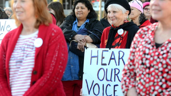 A woman holds up a sign at a rally held in honor of International Women's Day and A Day Without a Woman on March 8, 2017 at Reno City Plaza.