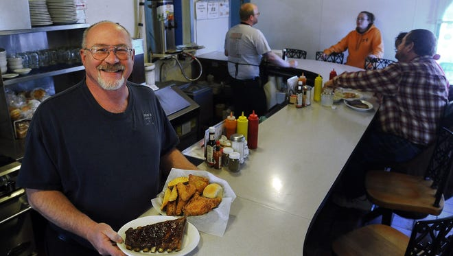 Ben Weiland holds fried chicken and ribs at Bob's.
