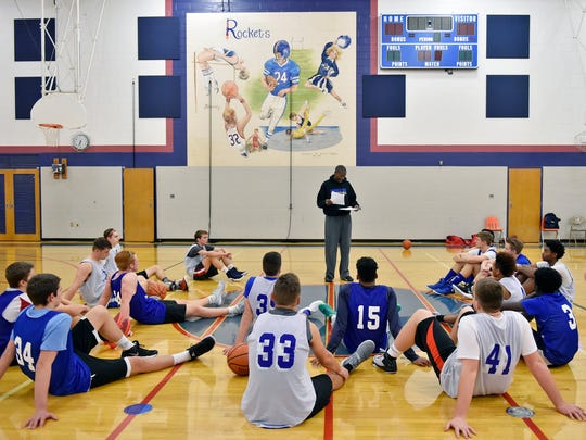 Head coach James Brooks reviews the previous night's games during basketball practice Wednesday, Dec. 14, 2016, at Spring Grove.