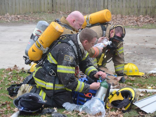 Firefighters work to revive a dog found in a house fire Thursday.