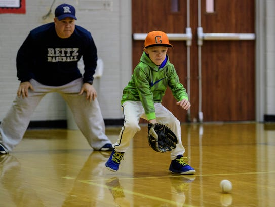 Jaydon Warren participates in a groundball drill as Todd DeWeese, the Reitz head baseball coach, observes his catch during the fourth annual Reitz Baseball Holiday camp at Reitz High School in Evansville, Ind., Wednesday, Dec. 27, 2017.