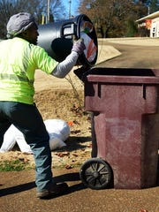 L.T. McNairy empties garbage into a Waste Management bin to take to the garbage truck during his route in Jackson in this December file photo.