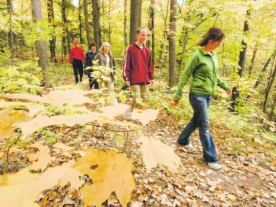 Elizabeth Maloney, right, of Minnesota leads her family along the Ice Age Trail during a Fall Colors Hike at the Dells of Eau Claire County Park in 2007.