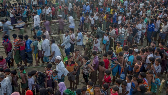 In this Sept. 25, 2017, file photo, Rohingya Muslims, who crossed over from Myanmar into Bangladesh, wait to receive aid during its distribution near Balukhali refugee camp, Bangladesh. International aid group Doctors Without Borders said Thursday, Dec. 14, 2017, its field survey has found at least 6,700 Rohingya Muslims were killed between August and September in a crackdown by Myanmar's security forces.
