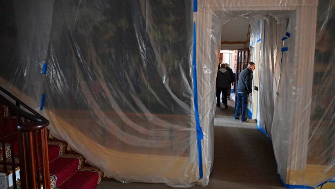 A visitor peeks inside Andrew Jackson's bedroom Jan. 18, 2018, as plastic sheeting covers the wallpaper in the entry hall of The Hermitage. Workers are installing a state-of-the-art fire suppression system that uses mist to extinguish fires inside The Hermitage.