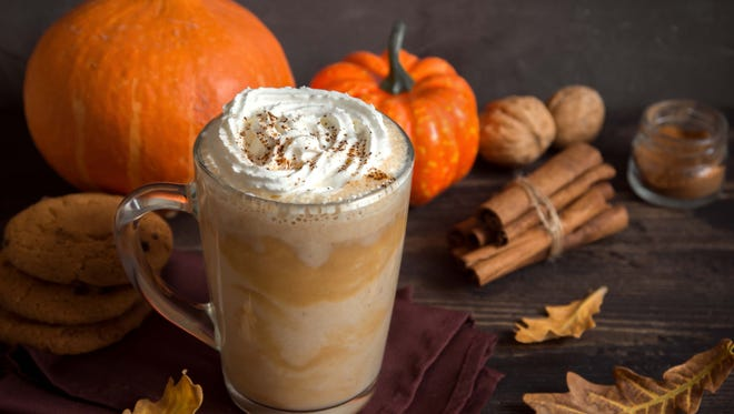 Pumpkin Spice Latte. Cup of Latte with Seasonal Autumn Spices, Cookies and Fall Decor. Traditional Coffee Drink for Autumn Holidays.