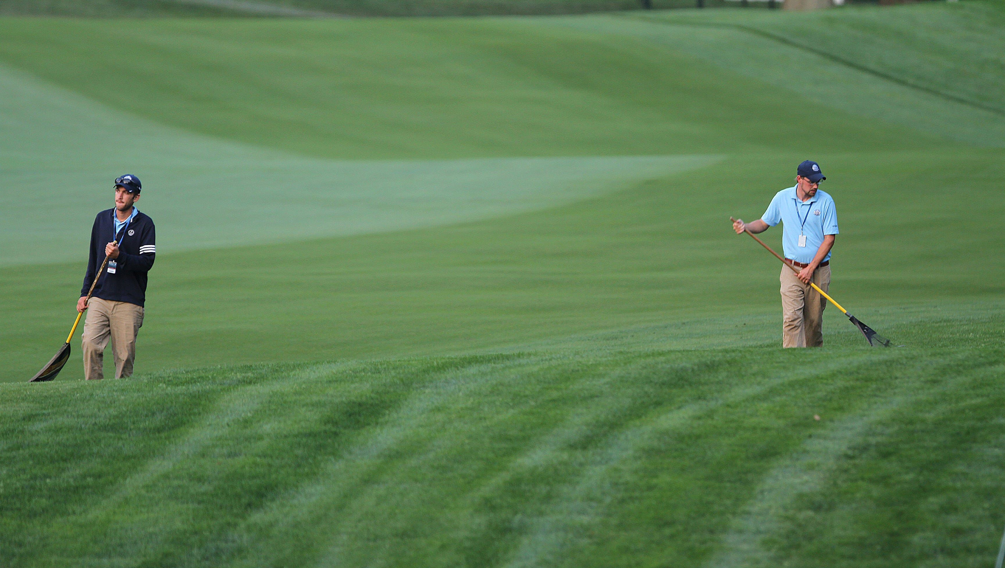Matt Giermak of Chicago, IL and bDennis Alexander of Chili groom 18 before the players arrived for their practice rounds Wednesday.