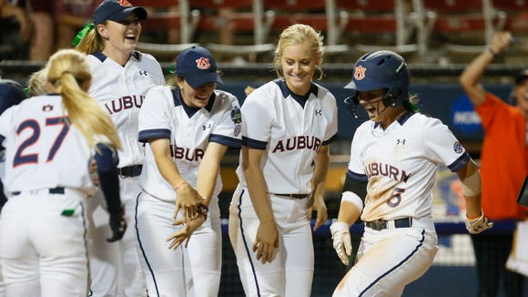 Auburn's Emily Carosone (5) is greeted by teammates as she crosses the plate following her game-winning home run in the eighth inning of the second game against Oklahoma in the best-of-three championship series in the NCAA softball Women's College World Series, in Oklahoma City, Tuesday, June 7, 2016. Auburn won 11-7. (AP Photo/Sue Ogrocki)