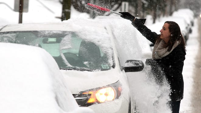 Danielle Paleafico of Morristown brushes snow off her car as the latest snow to hit New Jersey delayed school openings throughout Morris County. February 17, 2015.