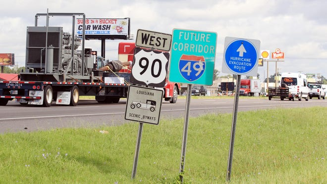 """A """"Future Corridor of I-49"""" sign is displayed among others as traffic moves north along Hwy. 90 in Broussard. September 10, 2014."""