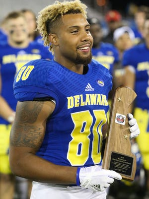Delaware receiver Diante Cherry poses with the Nate Beasley MVP trophy after he scored the only TDs in Delaware's 22-3 win against Delaware State at Delaware Stadium.
