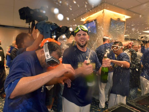 Mike Moustakas sprays the bubbly with his teammates in the locker room after hte Royals defeated the A's in the AL wild card game.