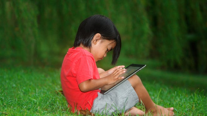 Boy child playing with tablet sitting on grass