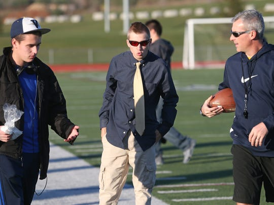Team managers Jake Rosser, left, and Zac Houliares, center, talk with assistant coach Paul Ojeda as the team moves through drills during practice at Victor High School Thursday, Nov. 17, 2016 in Victor.