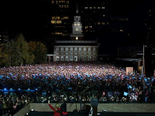 Democratic party nominee Hillary Clinton (L) walks on stage with US President Barack Obama during a rally on Independence Mall, November 7, 2016 in Philadelphia, Pennsylvania. About 40,000 people flooded Independence Mall in Philadelphia for Hillary Clinton's rally with her husband Bill, President Barack Obama and his wife Michelle at her side, a campaign aide said. The attendance set a new record for Clinton, with the previous high point a rally in Ohio that drew 18,500 people, a campaign aide told reporters traveling with the candidate.