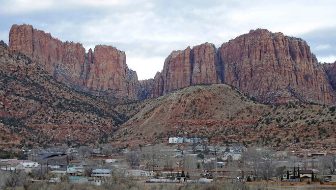 This Dec. 16, 2014, file photo, shows Hildale, Utah, sitting at the base of Red Rock Cliff mountains, with its sister city, Colorado City, Ariz., in the foreground.