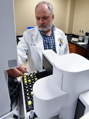 Forensic Scientist Associate Kevin Lewis uses gas chromatography