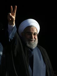Iranian President Hassan Rouhani flashes a victory