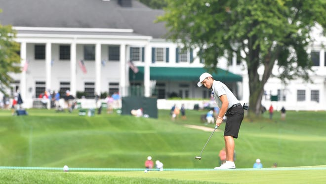 Sam Burns of Shreveport, La., putts on the 11th green with the Oakland Hills Country Club clubhouse in the background prior to the 2016 U.S. Amateur.