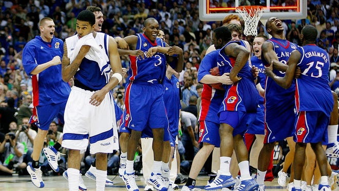 Memphis' Chris Douglas-Roberts, left, walks off the court as the Kansas players celebrate a victory in the NCAA Championship game in San Antonio, Texas, on April 7, 2008.