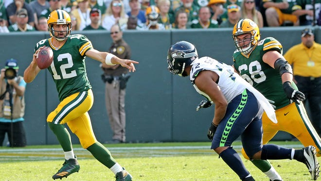 Green Bay Packers quarterback Aaron Rodgers (12) scrambles as offensive tackle Kyle Murphy (68) tries to block against the Seattle Seahawks defensive end Michael Bennett (72) Sunday, September 10, 2017 at Lambeau Field in Green Bay, Wis.