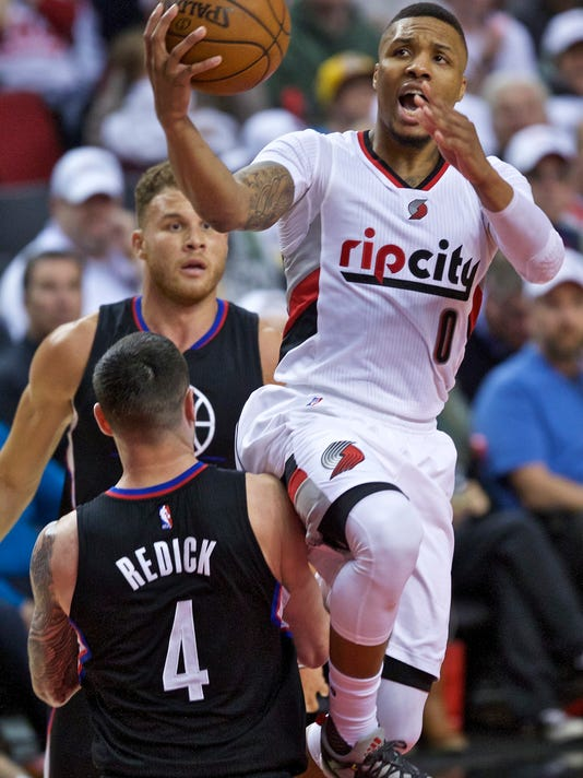 Portland Trail Blazers guard Damian Lillard, right, shoots over Los Angeles Clippers guard J.J. Redick, left, during the second half of Game 3 of an NBA basketball first-round playoff series Saturday, April 23, 2016, in Portland, Ore. (AP Photo/Craig Mitchelldyer)