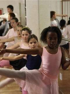 Children do stretch exercises at the balancing bar during a ballet class at the Dansazania Studio in Johannesburg. Cinda Eatock's project brings together children from Johannesburg's leafy suburbs, gritty inner city and once segregated townships, to learn ballet, hip-hop and tap dancing, whether or not they can pay.