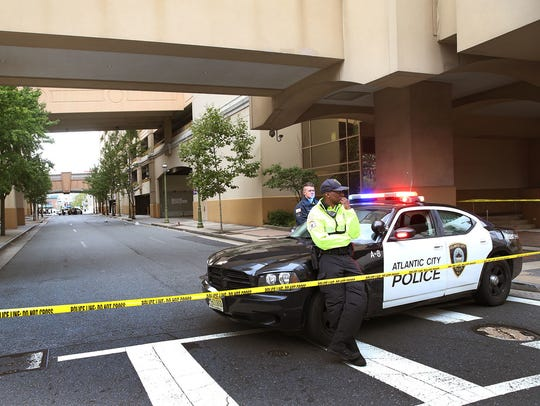 A police officer stands guard near the scene of a shooting
