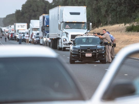 California Highway Patrol officers assist in the search for a second suspect following a shootout at a store in Los Molinos.