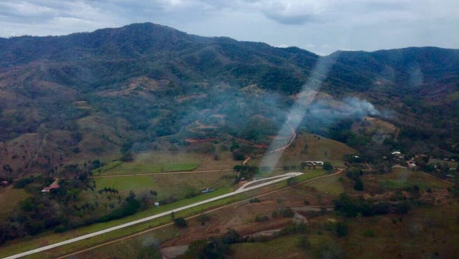 This photo released by Costa Rica's Public Safety Ministry shows smoke rising from the site of a plane crash near an air strip in Punta Islita, Guanacaste, Costa Rica, Sunday, Dec. 31, 2017. A government statement says there were 10 foreigners and two Costa Rican crew members aboard the plane belonging to Nature Air, which had taken off nearby. (Costa Rica's Public Safety Ministry via AP)