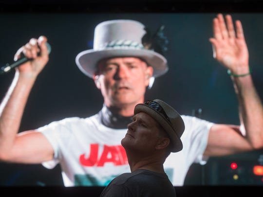 Lead singer Gord Downie is seen performing on a screen