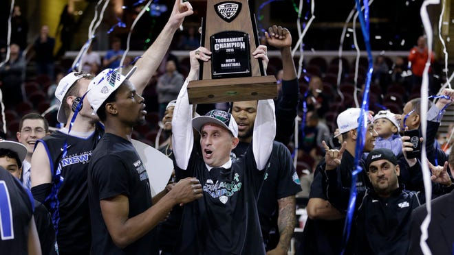 Buffalo head coach Bobby Hurley, center, and teammates celebrate after Buffalo defeated Central Michigan 89-84 Saturday in an NCAA college basketball game in the championship of the Mid-American Conference tournament.