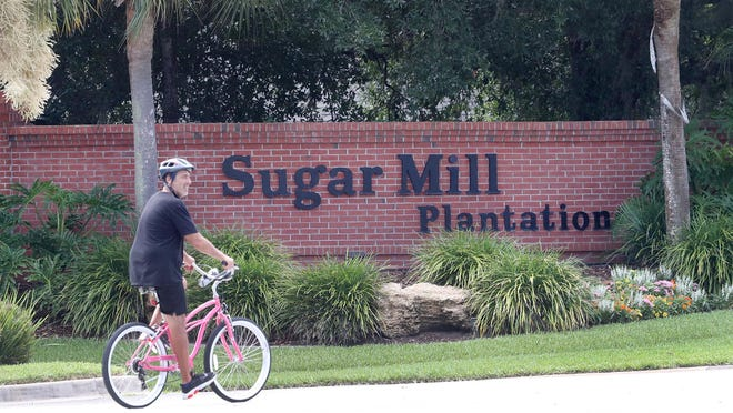 "A bicyclist peddles past the entrance to the Sugar Mill Plantation on Old Kings Road in Flagler County on Wednesday, July 1, 2020. It is one of several ""plantation"" communities in the area that was home to the historic Bulow Sugar Mill Plantation in the early 1800s."