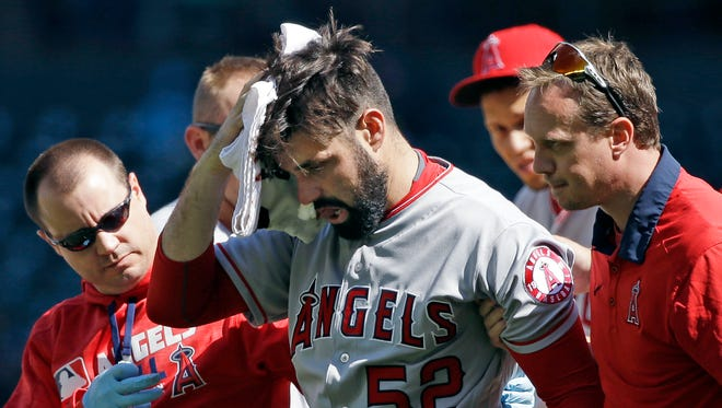 Los Angeles Angels starting pitcher Matt Shoemaker is assisted off the field after being hit by a line drive against the Seattle Mariners on Sept. 4, 2016, in Seattle.