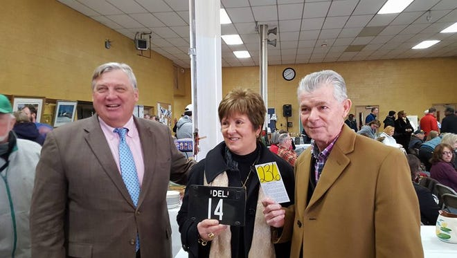 Auctioneer Butch Emmert, left, stands with Donna and Ray White, who submitted the winning bid for Delaware vehicle tag No. 14. They paid $325,000.