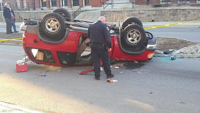 Officials and onlookers inspect the scene of a crash on Philadelphia Street outside Helen Thackston Charter School around 5:15 Monday evening.